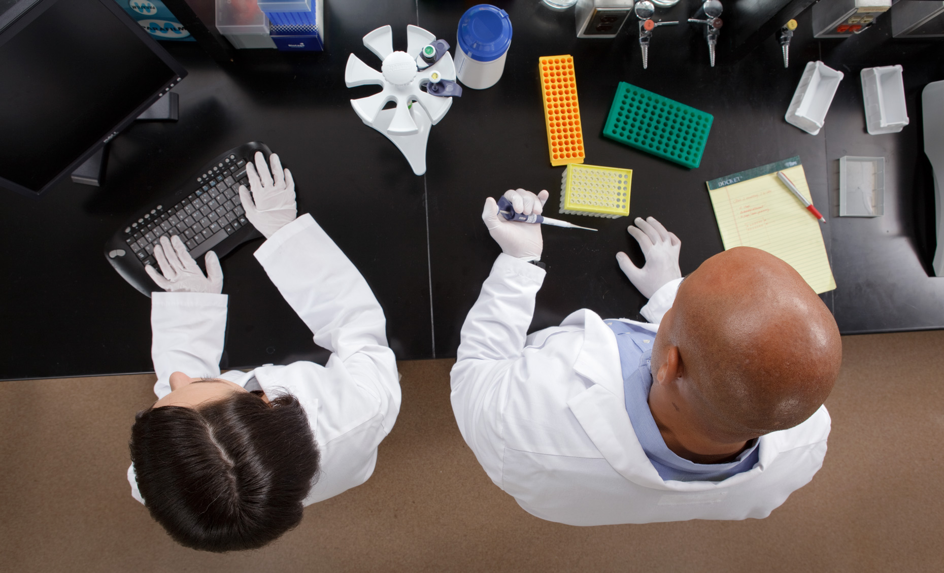 Overhead view of two people working in a laboratory.
