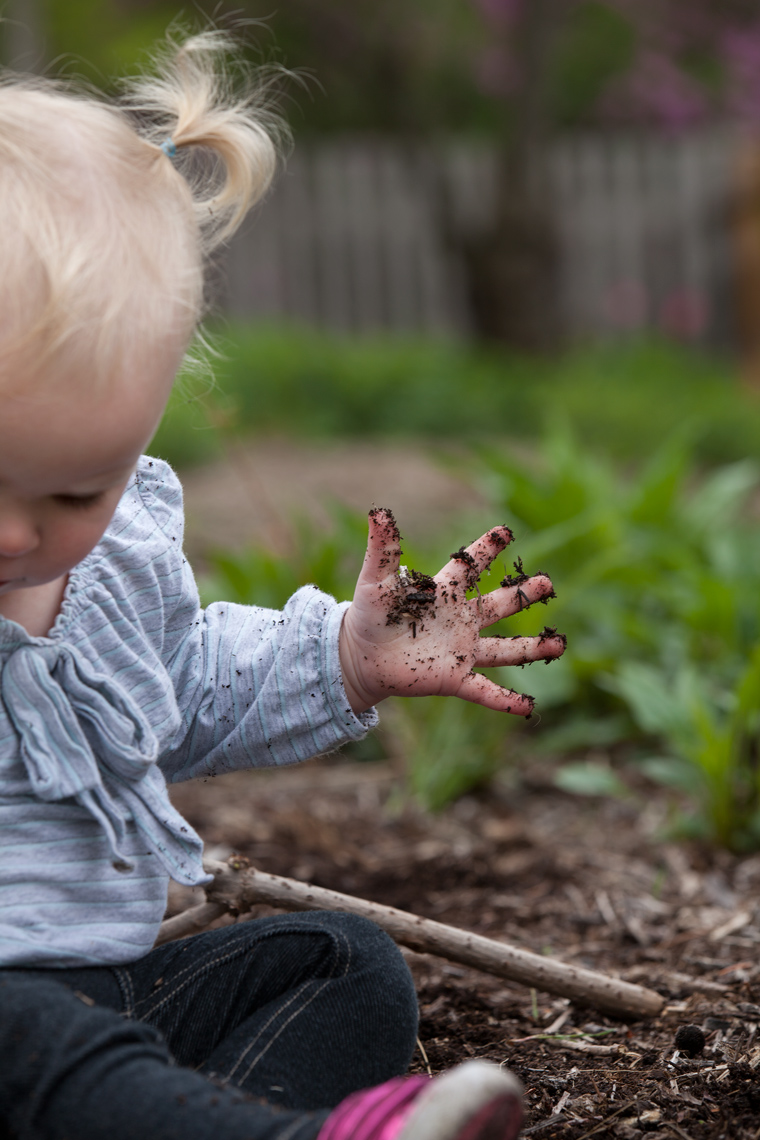 Little girl with blonde playing in dirt.