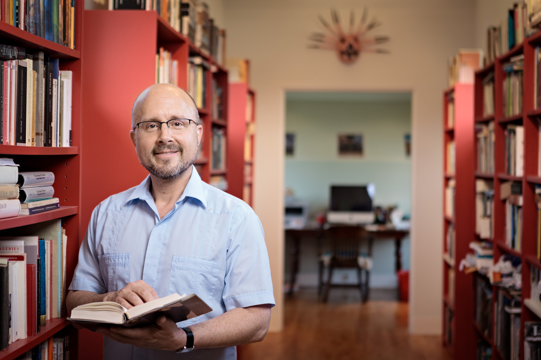 Man with book standing in home library.