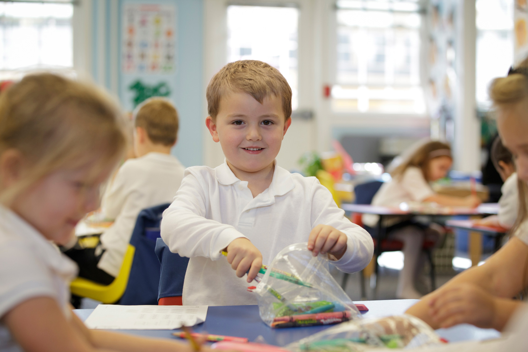 Kindergarten boy in white shirt with crayons in school.