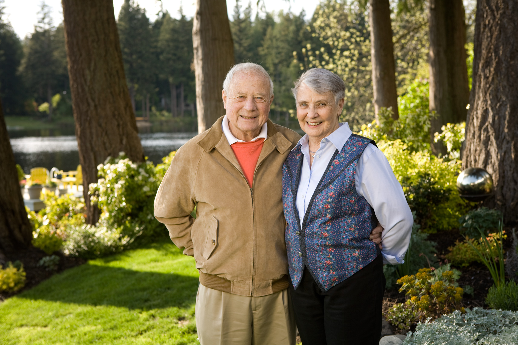 Couple standing in backyard with late afternoon light and large trees.