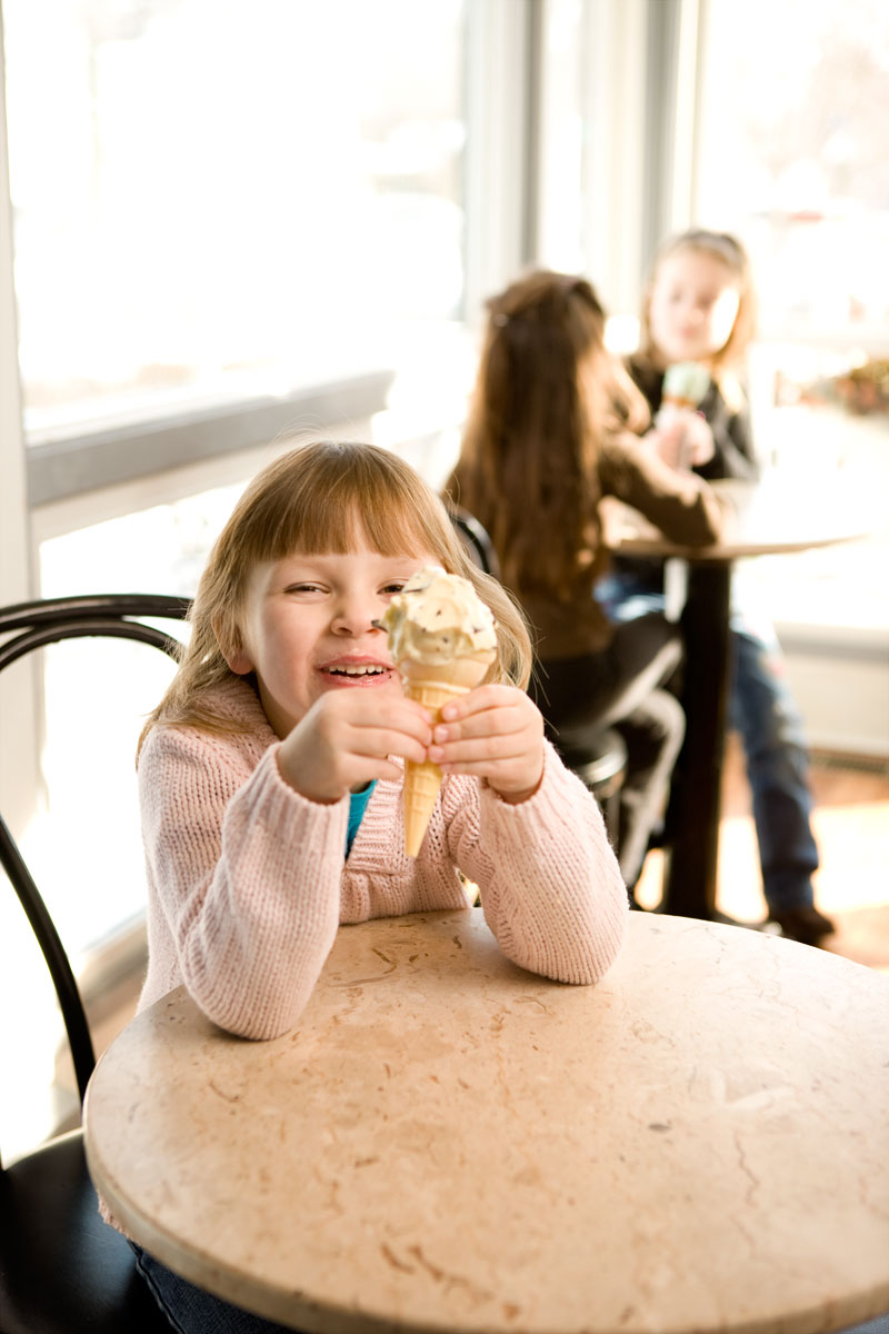 Girl eating ice cream inside ice cream parlor.
