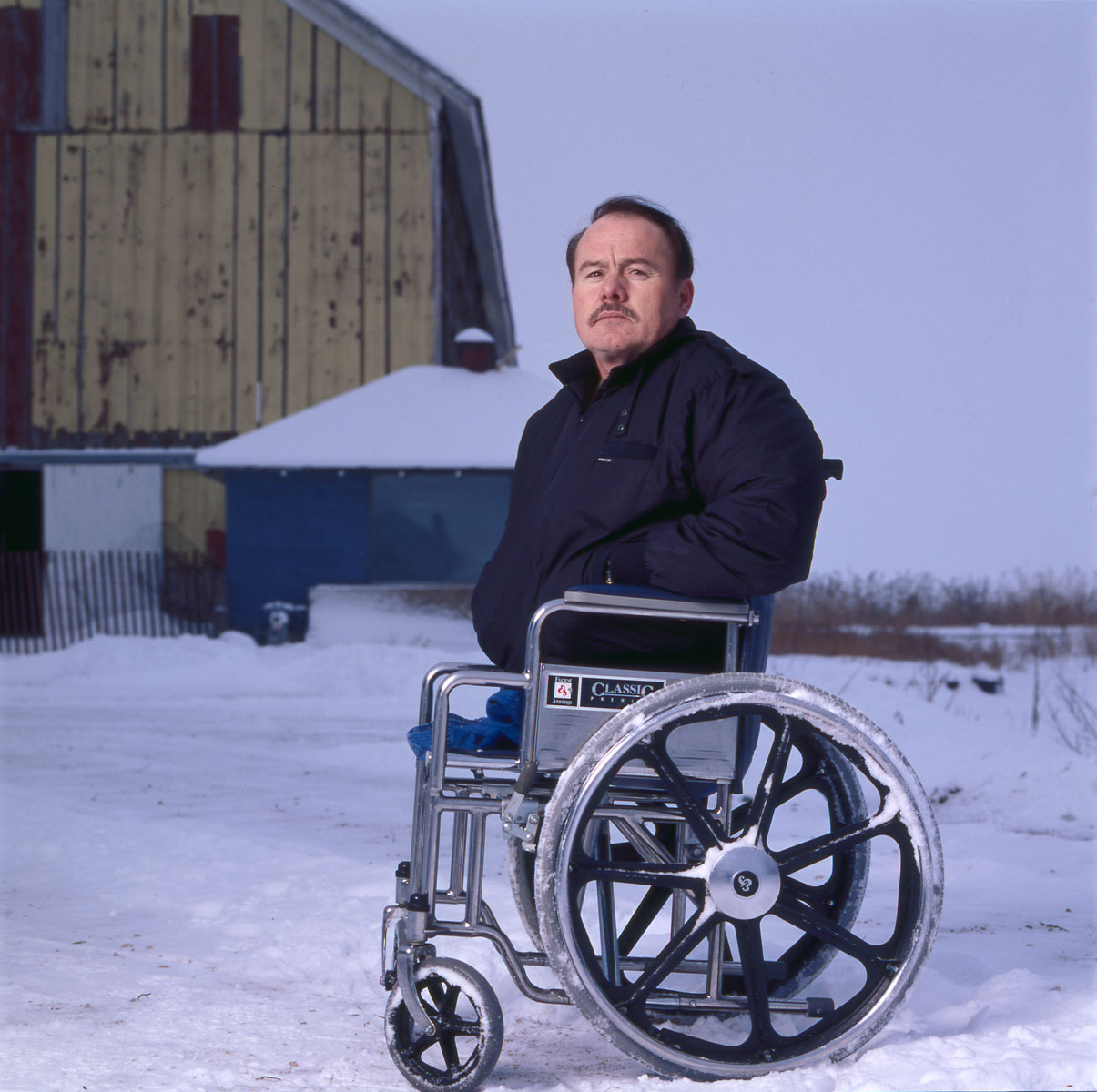 Man in wheelchair sitting in front of snowy barn.