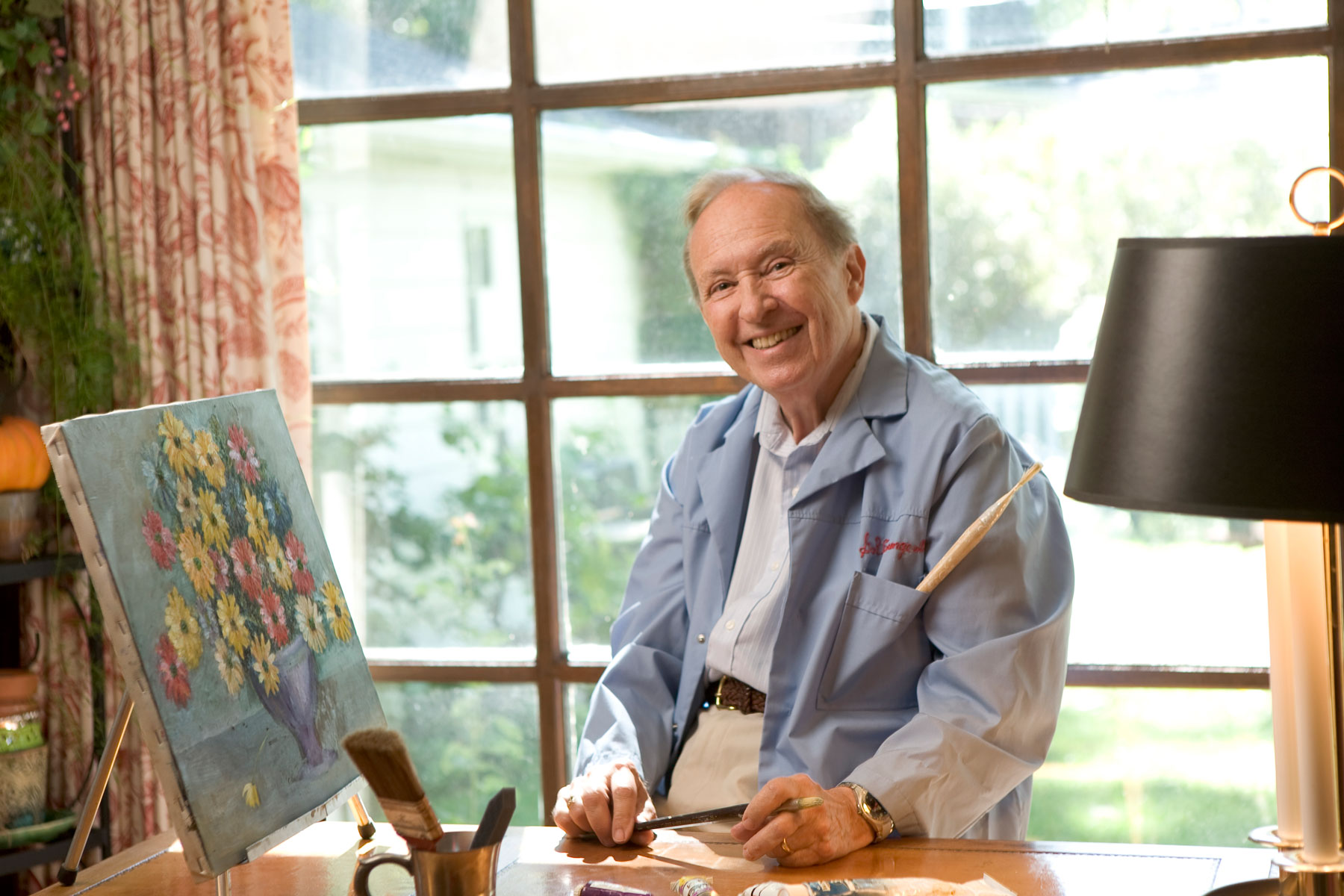 Artistic man in blue jacket painting at a desk in front of window.