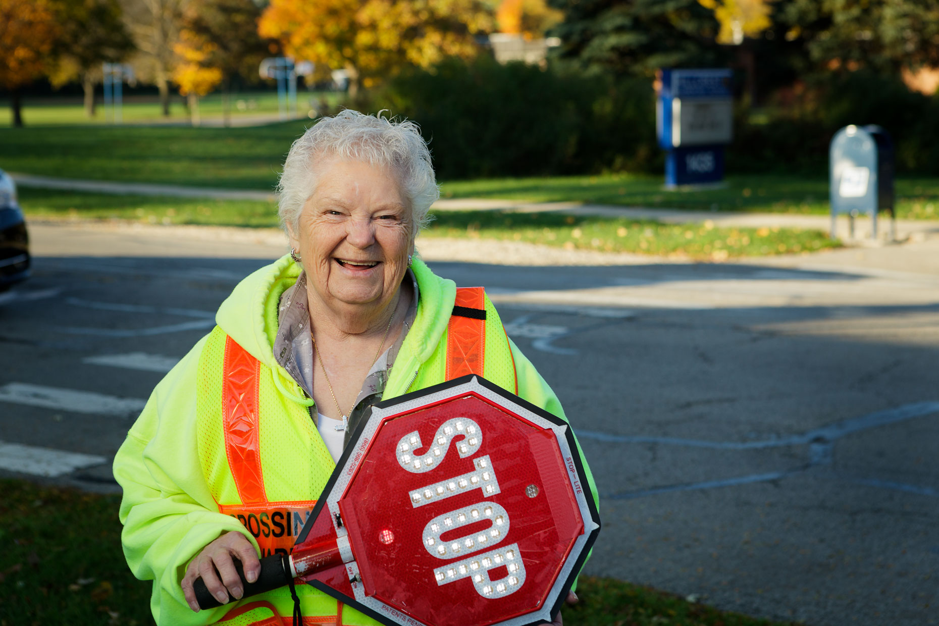Crossing guard with stop sign standing outside in residential neighborhood.